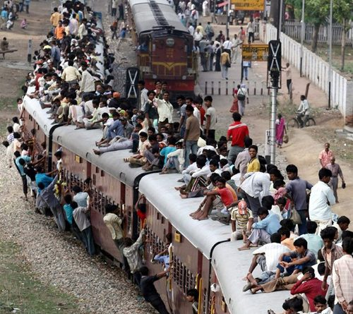People travel on a crowded passenger train in Lucknow